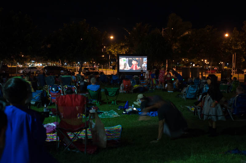 Families watch an outdoor movie on the lawn.