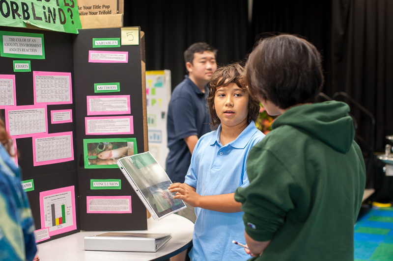 Student explaining research project to science fair judge