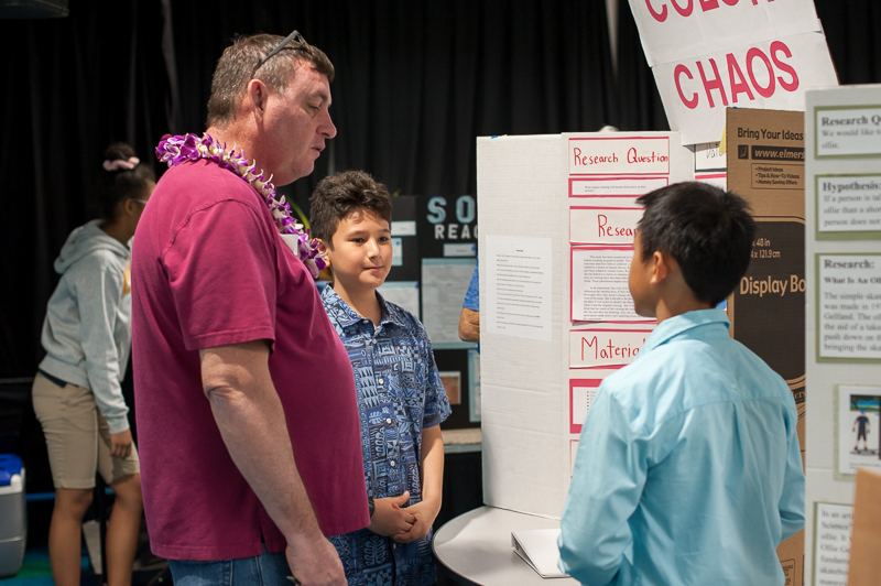 Students explaining research project to science fair judge