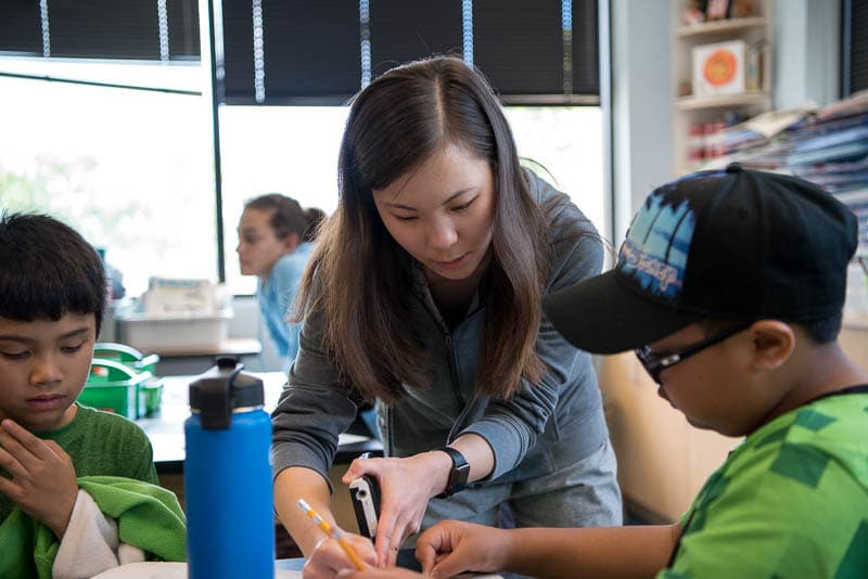 A senior student helps younger students with a math problem