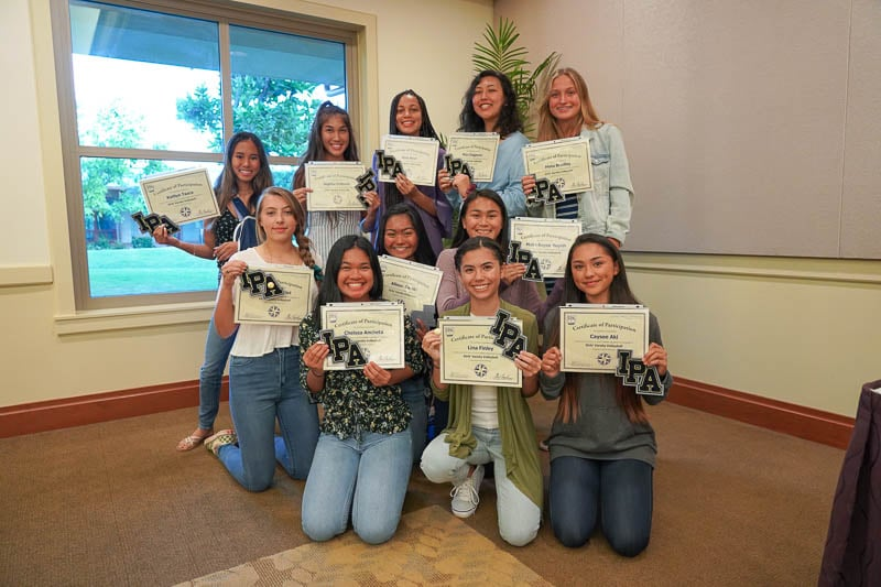Girlsʻ varsity volleyball team showing off their certificates.