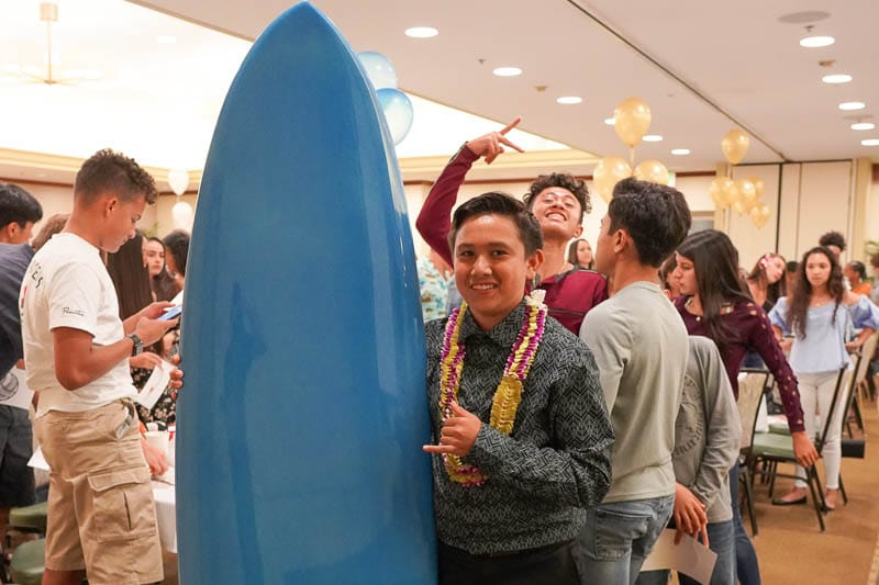 Student stands next to surfboard prize