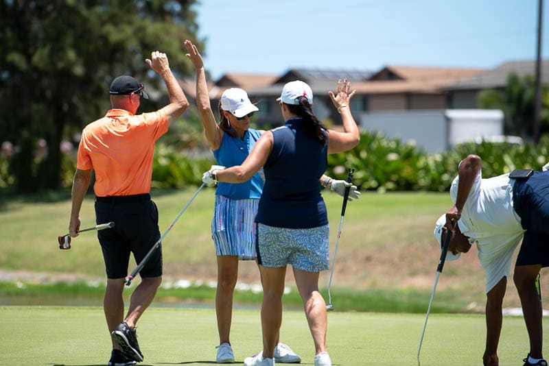 Foursome gives high fives after putt