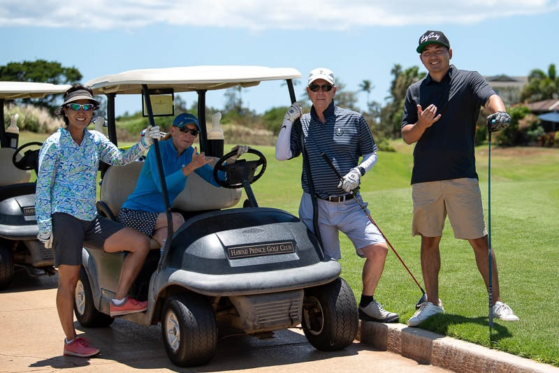 Foursome poses for photo in front of golf cart