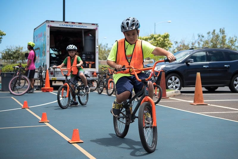 A Grade 4 student rides bike through cones