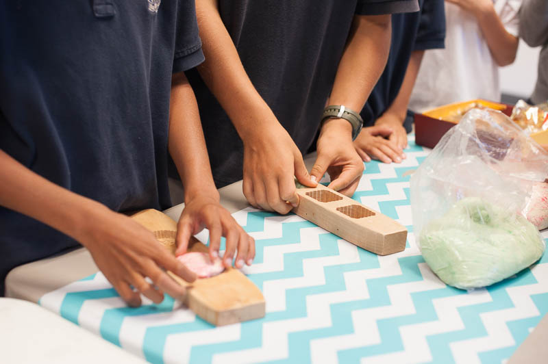 Student hands pressing dough into wooden molds.