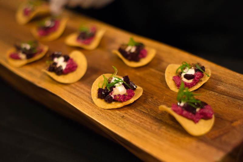 Mini beet tostadas on a wooden serving tray.