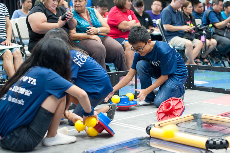 Students prepare the robotics competition field.