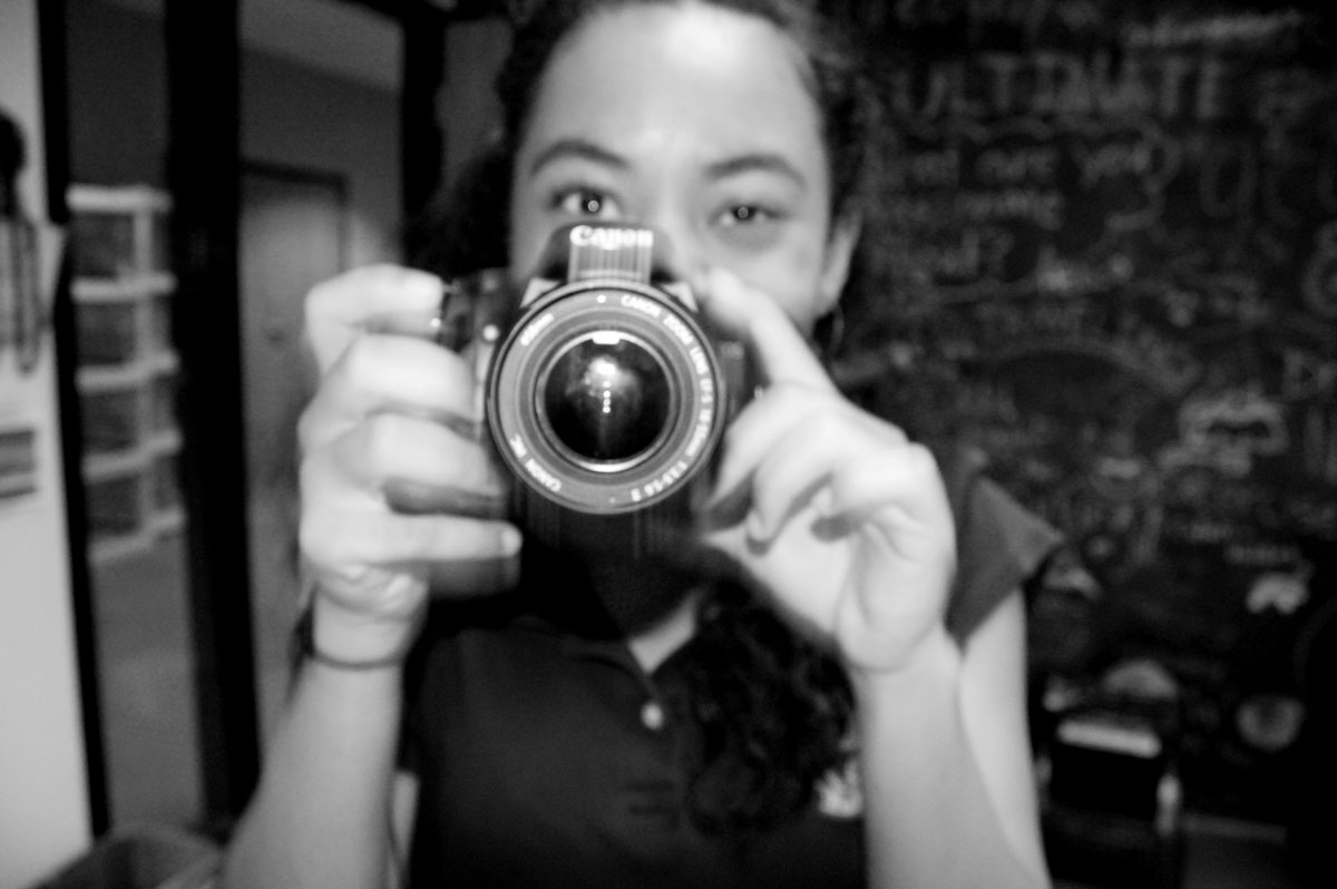Black and white photo of student with camera