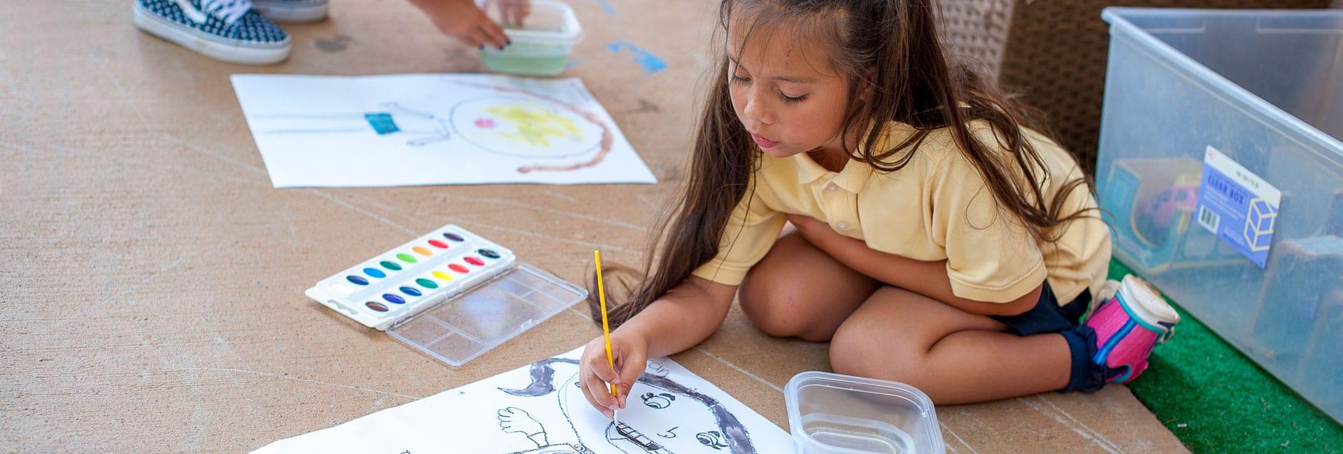 Little girl painting outside on sidewalk