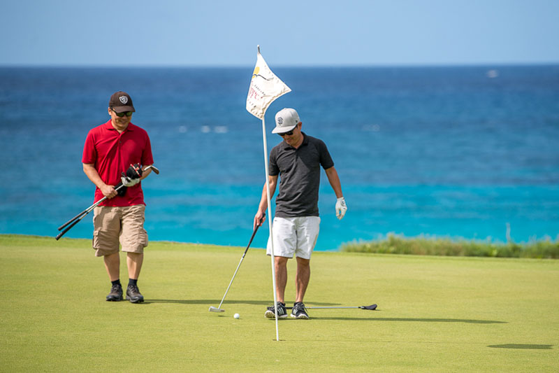 Golfers on the green with ocean backdrop