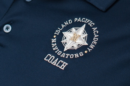 Embroidered logo of coach's shirt