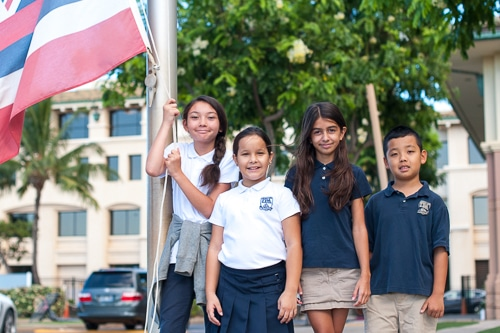 Students raising the flag in front of school