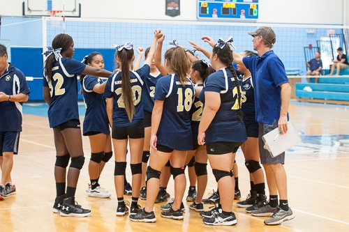 Girls volleyball team in huddle