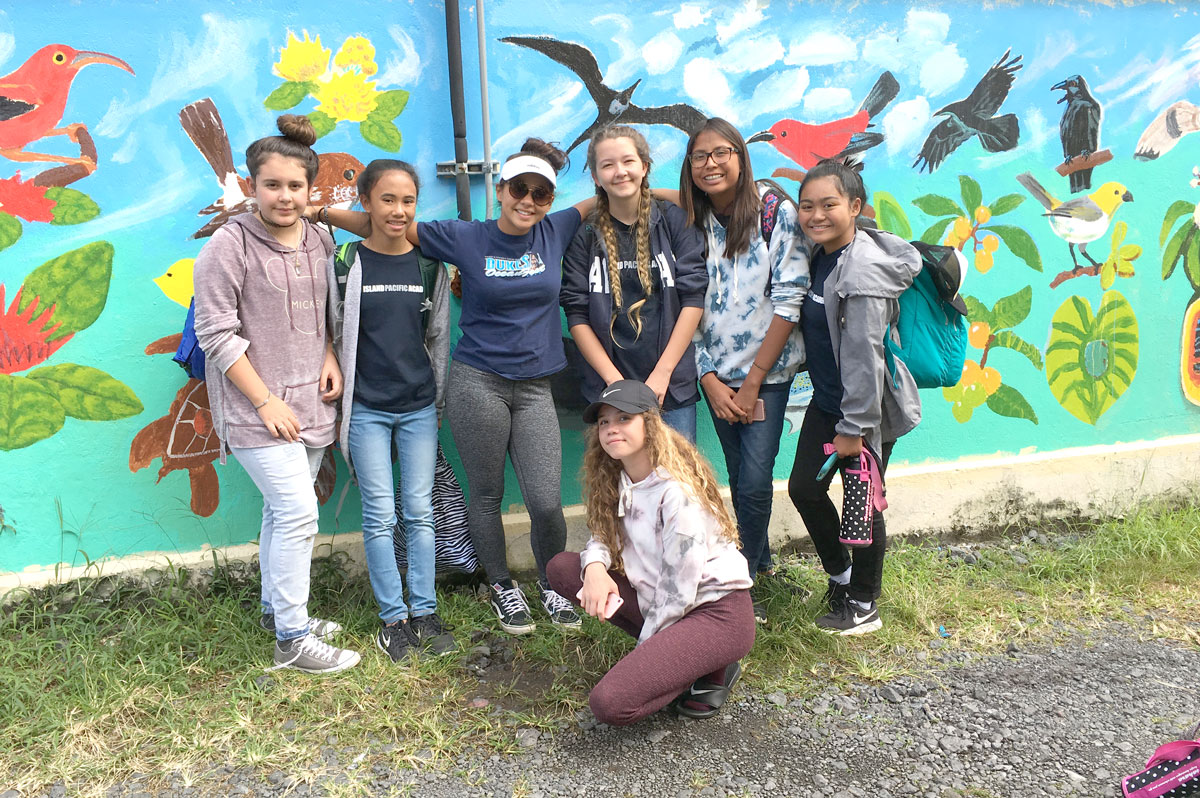 Grade 8 students standing in front of mural of Hawaiian forest birds on Big Island