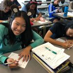 Student in Japanese class learning calligraphy.