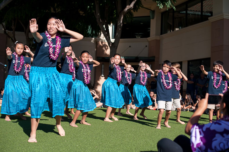 Students dance hula on grass