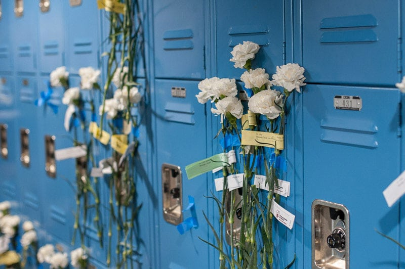 White carnations taped to student lockers