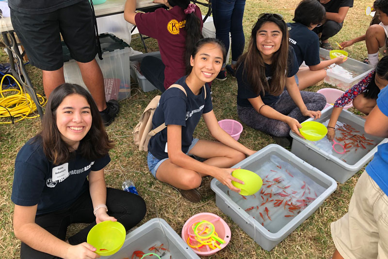 Students volunteering at fish game booth