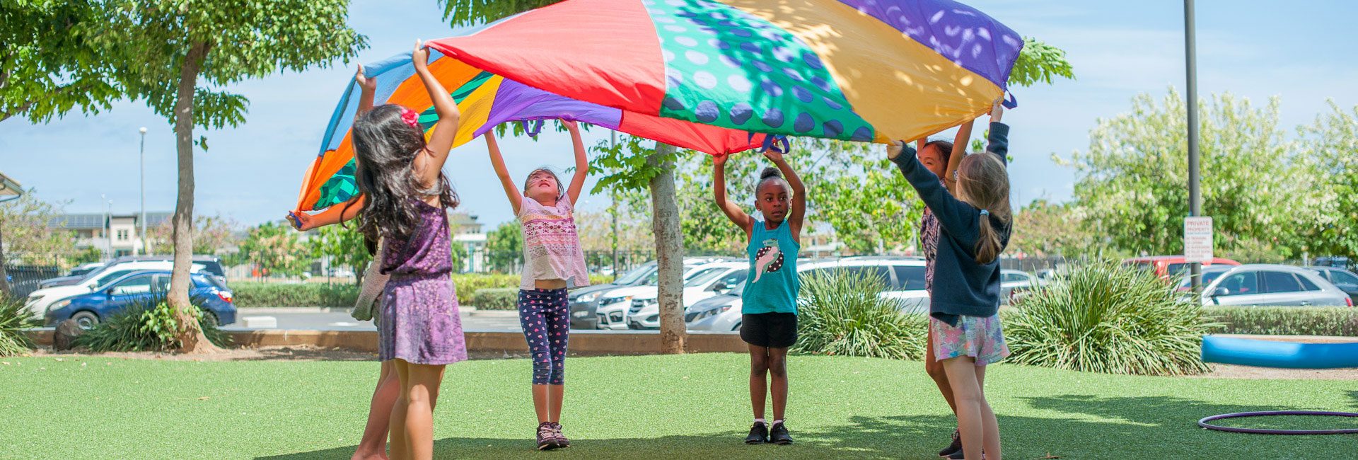 Elementary students playing with a colorful parachute on the grass