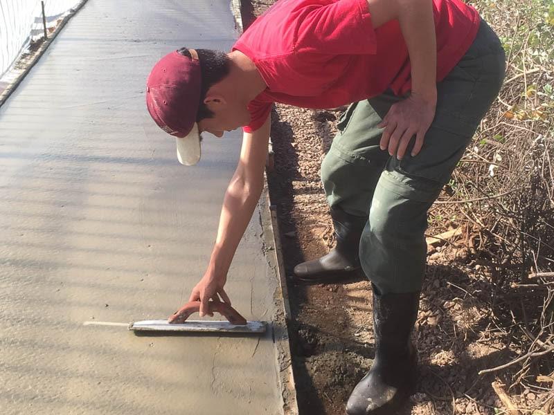 Ashton Yamamura smooths the wet concrete