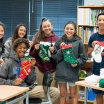 Students holding up handmade holiday stockings.