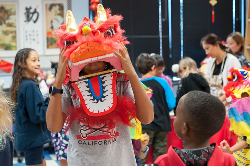 Student with lion head performing Chinese lion dance