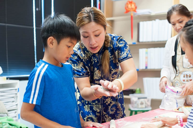 Mandarin teacher showing student how to fold dumplings
