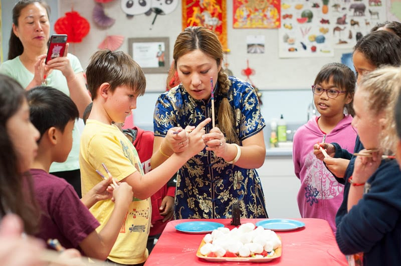 Mandarin teacher helps student use chopsticks