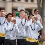 Students blowing conch shells to open May Day celebration