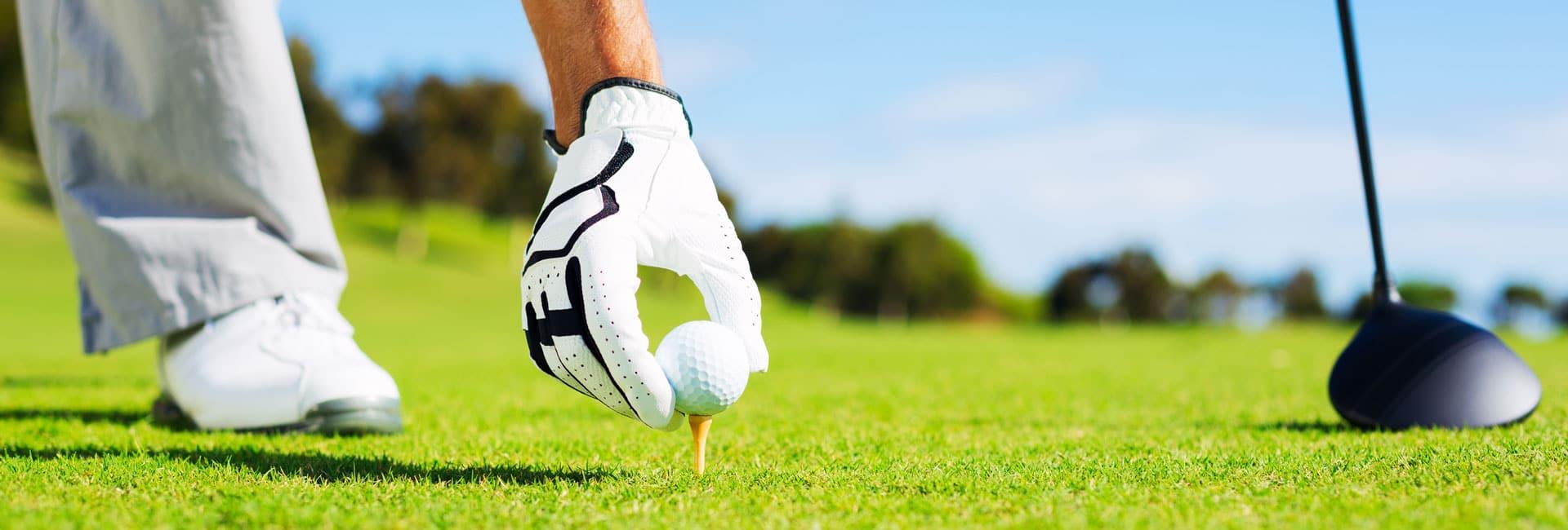 Golfer teeing up ball