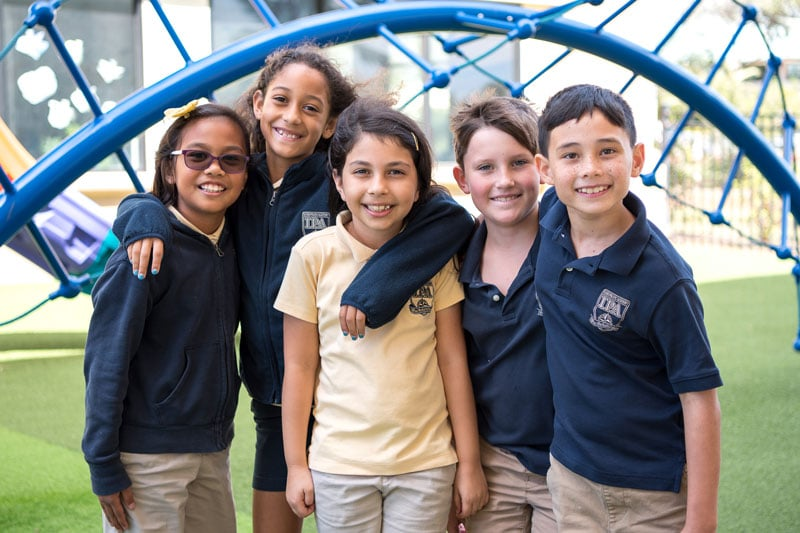Five elementary students smiling on playground