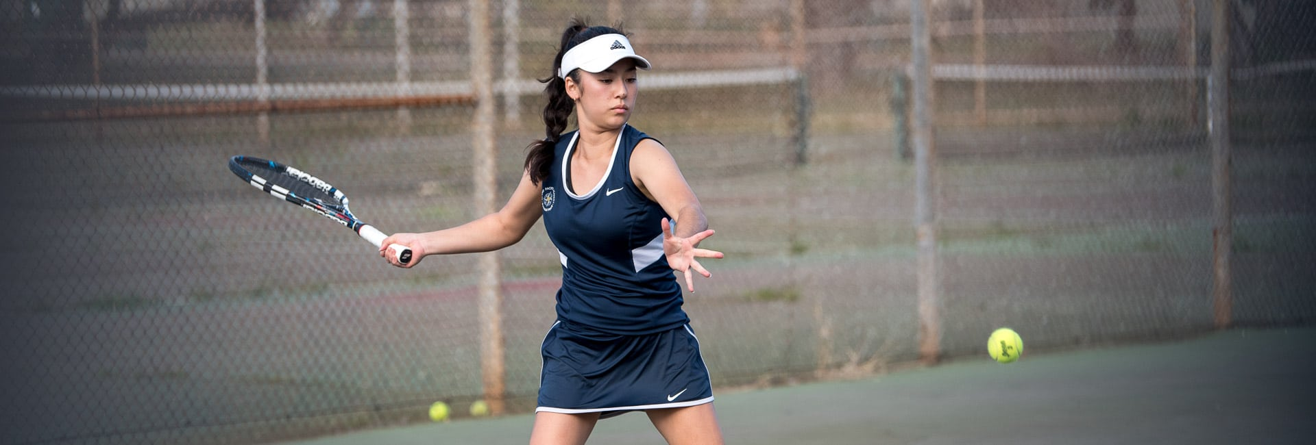Varsity girls tennis player hitting forehand