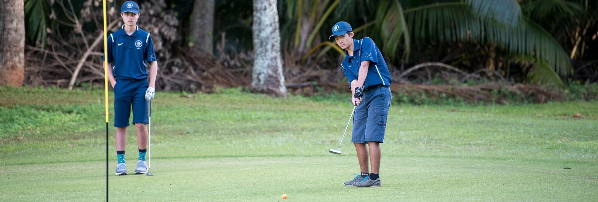 Intermediate boy golfer putting