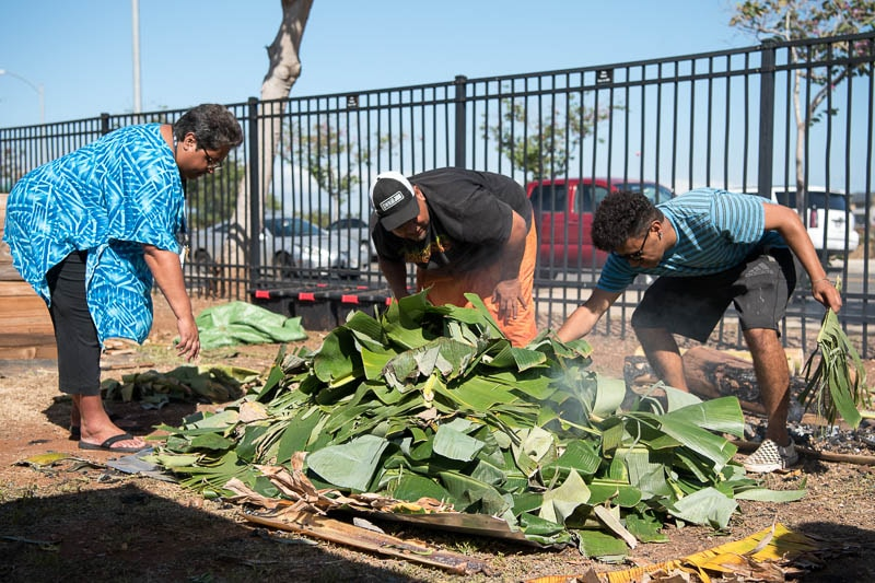 Saʻo, Ashley, and their son cover the food with banana leaves to insulate the umu