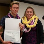 Swimmer with coach showing off certificate