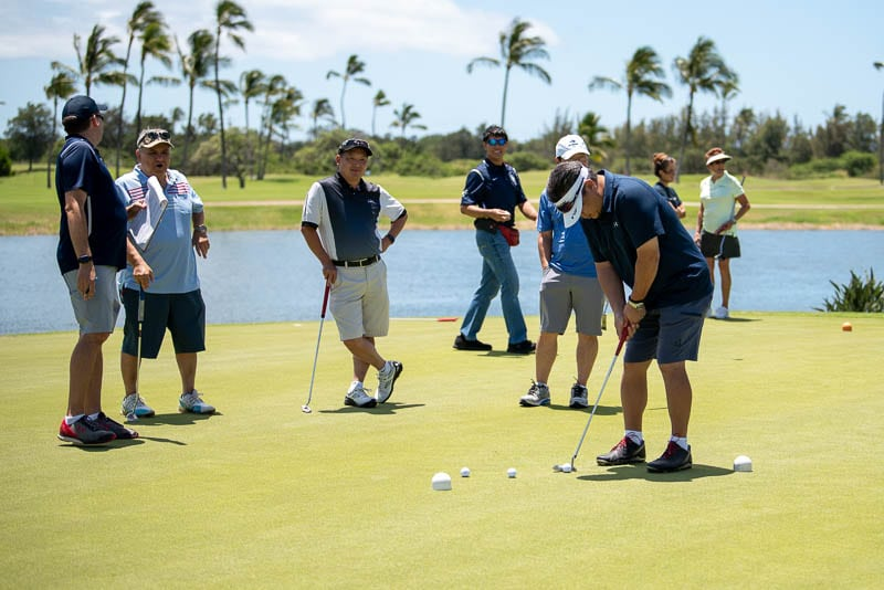 Golfers on putting green waiting their turn