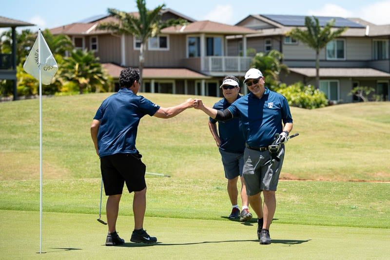 Foursome gives fist bumps after sinking a putt