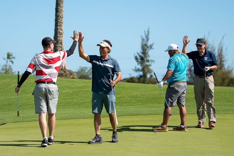 Foursome gives high fives after sinking a putt