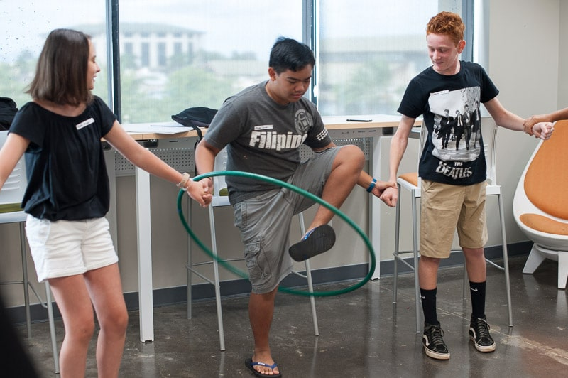 Upper school students play a hula hoop icebreaker game at new student orientation