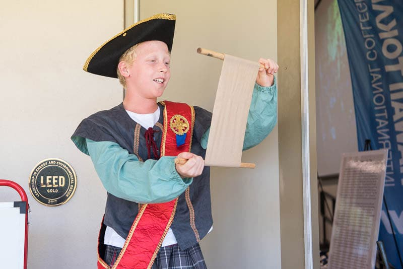 Student dressed as town crier reads a proclamation