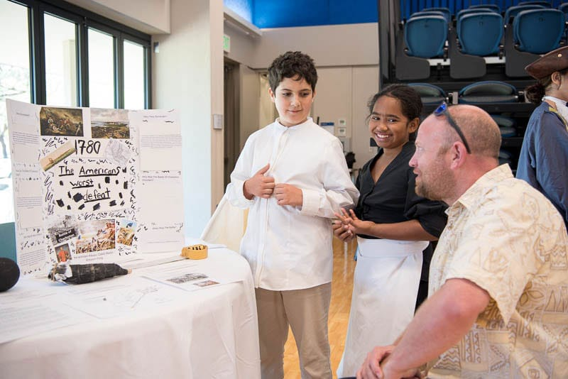 Students explain their exhibit to a museum visitor