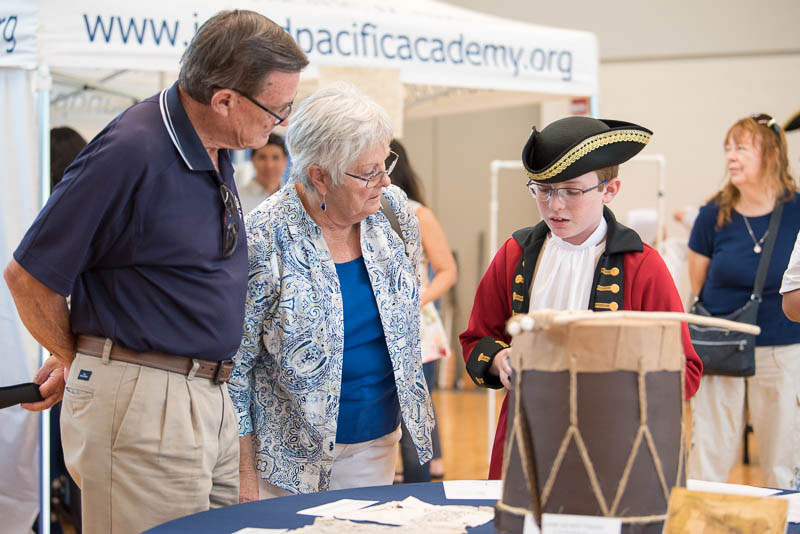 Student in red coat costume explains Revolutionary War exhibit to museum visitors