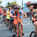 Grade 4 students in helmets and safety vests on their bikes