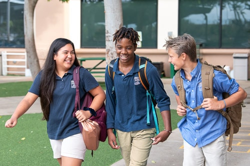 Three middle school students walking on campus