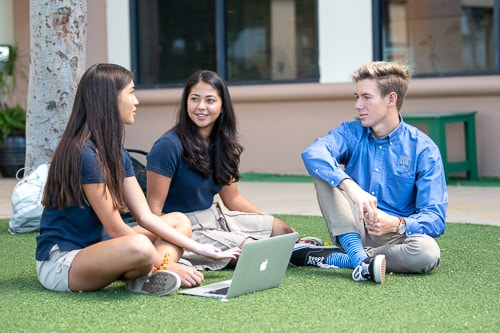 Three high school students sitting on the grass talking.