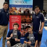 IPA Navigator Robotics team members and coach pose with tournament awards and robots