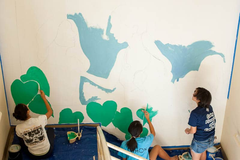 Three students painting a mural in hospital stairwell