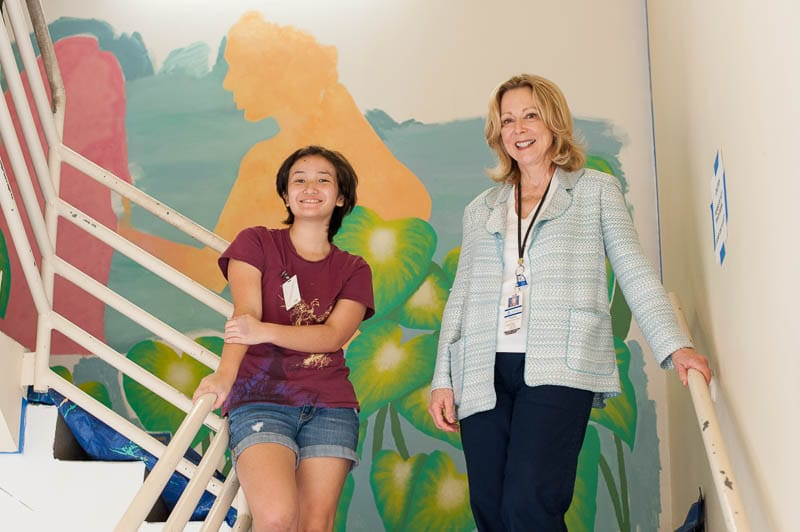 Annie Uesugi and Susan Murray in hospital stairwell in front of mural