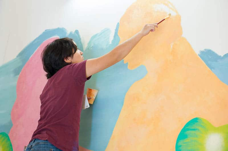 Student painting a figure in wall mural